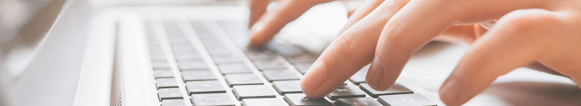 Hands typing on a laptop keyboard.