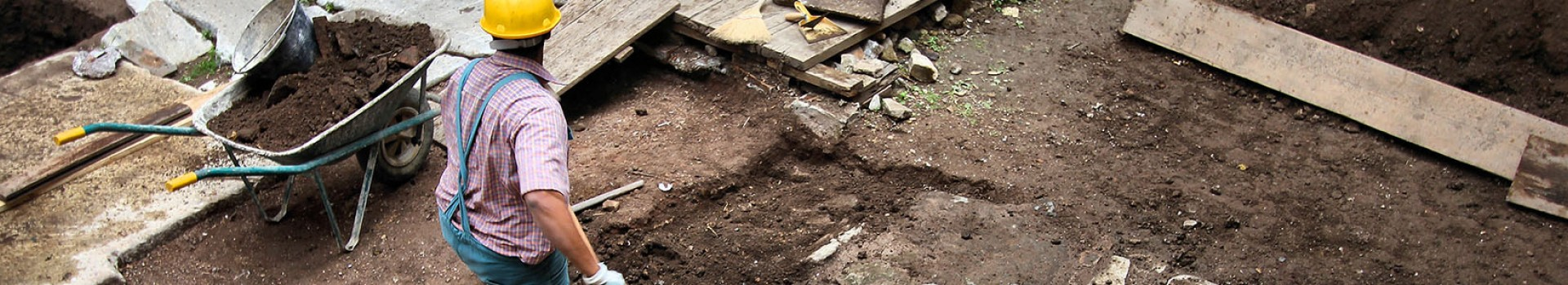 An archaeologist digs next to a barrow.