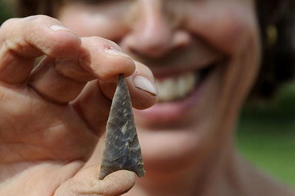 Smiling archaeologist holding a flint arrowhead.
