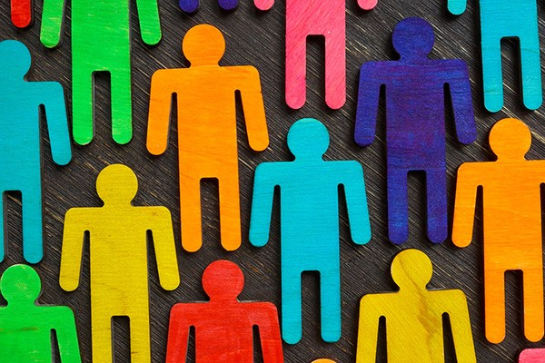 Coloured people-shaped cut-outs on a dark blue background.