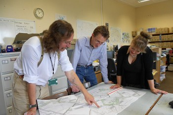 Member-level archaeologists examine plans in an office.
